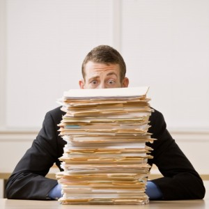 manage-sharepoint-content | Photo Courtesy of ThinkStock http://www.thinkstockphotos.com/image/stock-photo-businessman-behind-stack-of-file-folders/152977163/